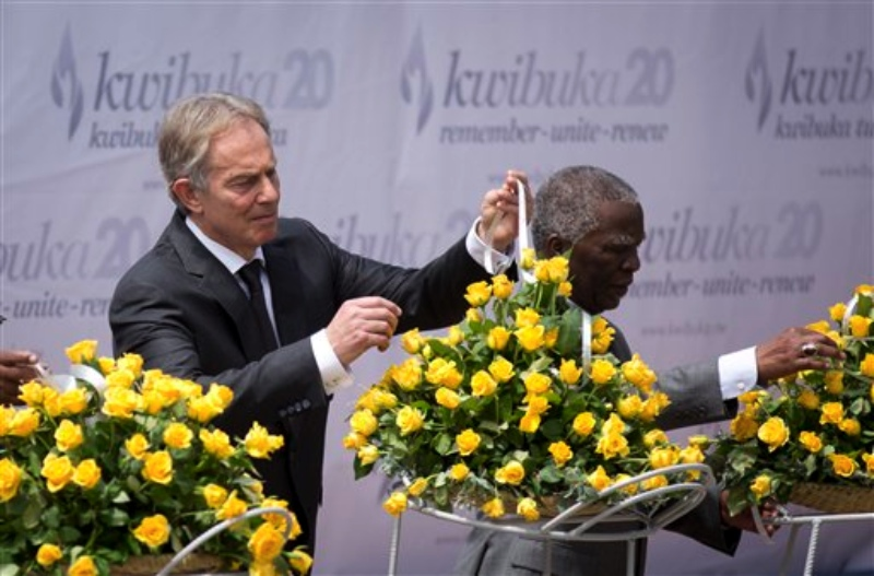 Former British Prime Minister Tony Blair, left, and Former South African President Thabo Mbeki, right, lay a memorial wreath at a ceremony to mark the 20th anniversary of the Rwandan genocide, held at the Kigali Genocide Memorial Center in Kigali, Rwanda Monday, April 7, 2014. (AP Photo/Ben Curtis)